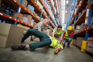 Workers tending to a injured employee on the floor in a warehouse